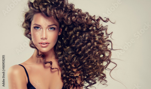 Fototapeta Brunette girl with long and shiny curly hair . Beautiful model with wavy hairstyle .  obraz