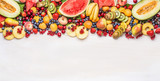 Fototapeta Fototapety do kuchni - Variety of colorful organic fruits and berries on white table background, top view, border. Healthy food and vegetarian eating concept
