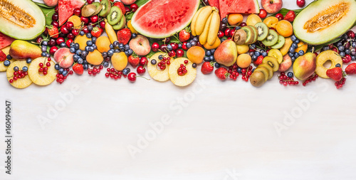Poster Fruits Variety of colorful organic fruits and berries on white table background, top view, border. Healthy food and vegetarian eating concept