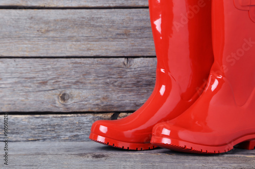Fotografía  Red rubber boots on a grey wooden table