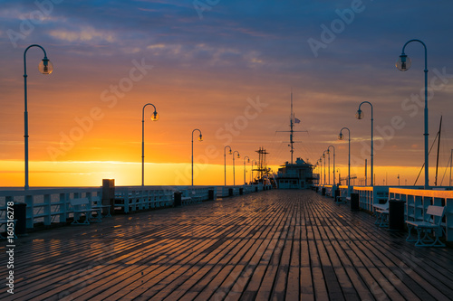 Fototapety, obrazy: The first rays of the sun warms the wet boards of the pier in Sopot. Poland.