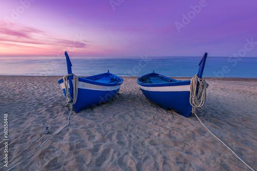 Foto op Aluminium Strand Blue wooden fishing boats on beach