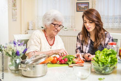 Poster Cuisine Grandmother and granddaughter preparing food together at kitchen.