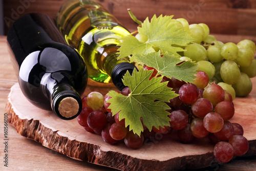 butelka-bialego-i-czerwonego-wina-obok-winogron-na-drewnianym-stole