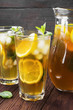 Ice tea with lemon and mint on a wooden background