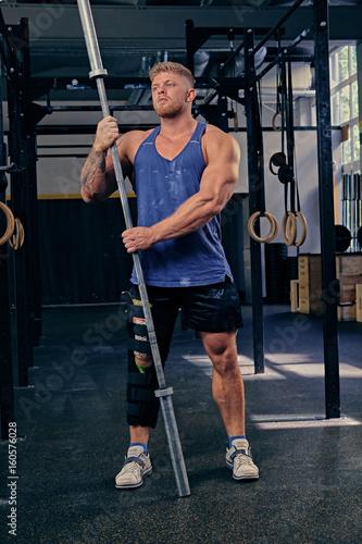 Fototapety, obrazy: Bodybuilder with injured leg holds barbell.