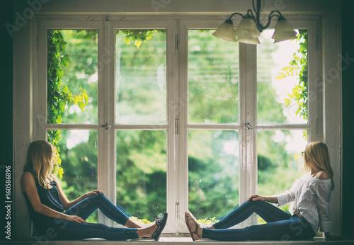 2 Junge Frauen Sitzen Auf Der Fensterbank Und Schauen Nach Draussen