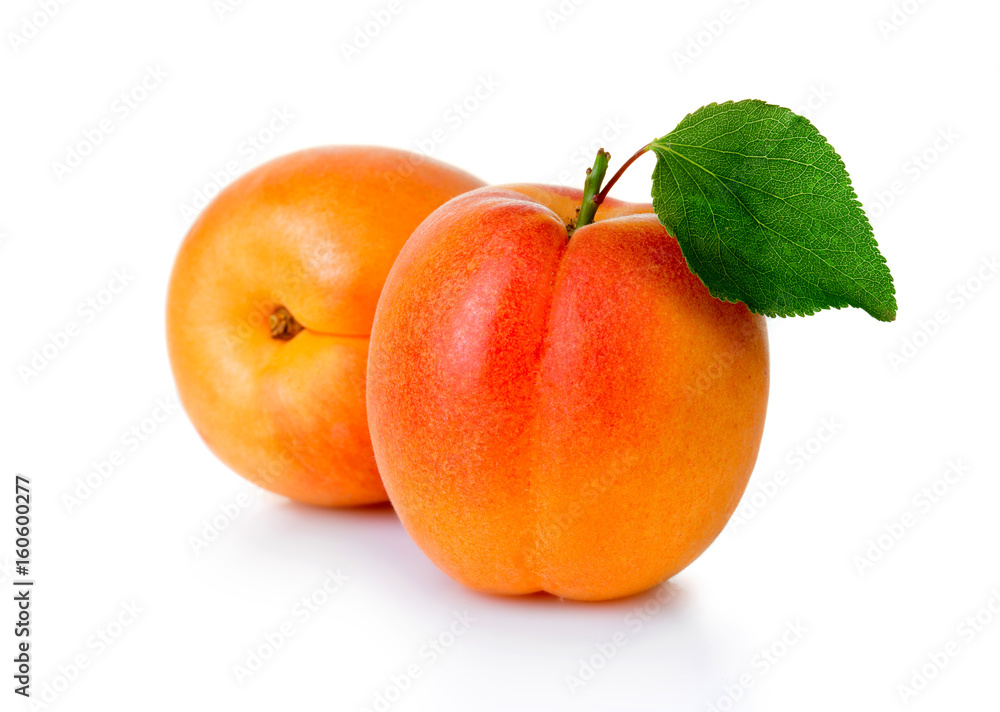 Fotografia Ripe apricot fruits with green leaf isolated on white