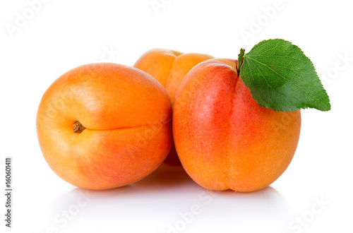 Ripe apricot fruits with green leaf isolate on white