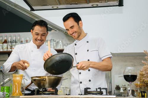 Plakat Dwóch młodych szefów kuchni przygotowuje i gotuje jedzenie w kuchni restauracji