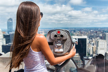 New York City Tourist Travel Woman Looking At View Of Skyline With Binoculars From Skyscraper Rooftop Building. Girl Traveling In USA Summer Holidays Trip.
