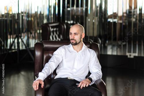 Fotografía  Man, bald, brutal, sits in a Chair.