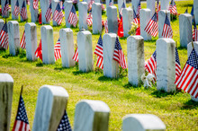 Rows Of Grave Markers With American Flags In Military Cemetery