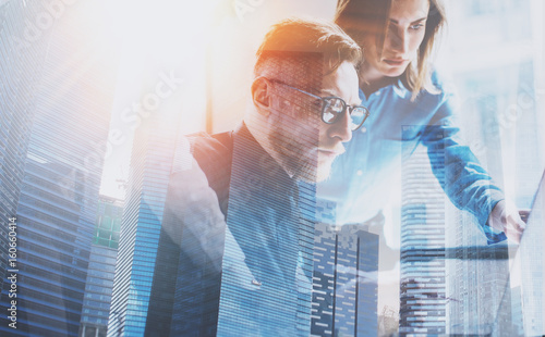 Group of three young coworkers working together at modern coworking office.Teamwork concept.Double exposure,skyscraper building blurred background.Flares effect.Horizontal.