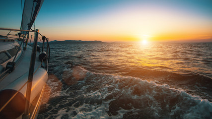 Slide sailing yacht through the waves of the sea during sunset.