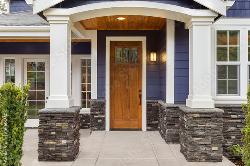 New Luxury Home Exterior Detail: New House Front Door And Covered Patio  With Arch,