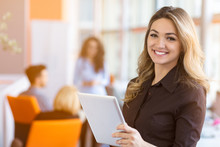 Portrait Of Young Business Woman At Modern Startup Office Interior, Team In Meeting In Background
