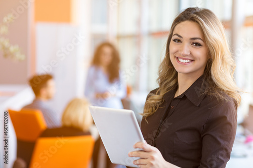 Obraz portrait of young business woman at modern startup office interior, team in meeting in background - fototapety do salonu
