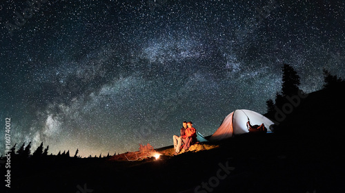 Poster Camping Night camping. Romantic couple tourists have a rest at a campfire near illuminated tent under amazing night sky full of stars and milky way. Astrophotography. Picture aspect ratio 16:9