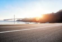 Empty Road Near Suspension Bridge With Sunbeam