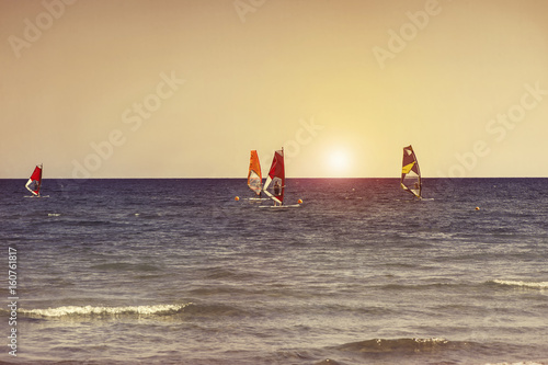 Windsurfers in the sea on Cyprus on sunset. Windsurfing in Larnaca