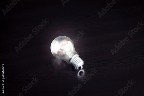 Fototapety, obrazy: Light bulb on dark background.