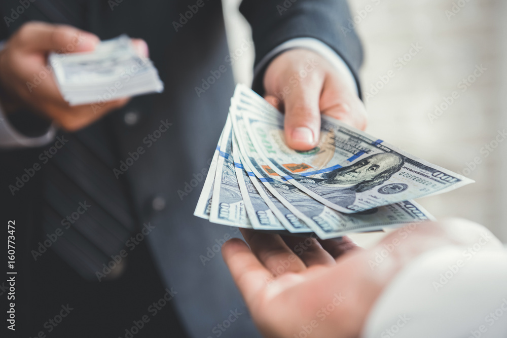 Fototapeta Businessman giving or paying money to a man