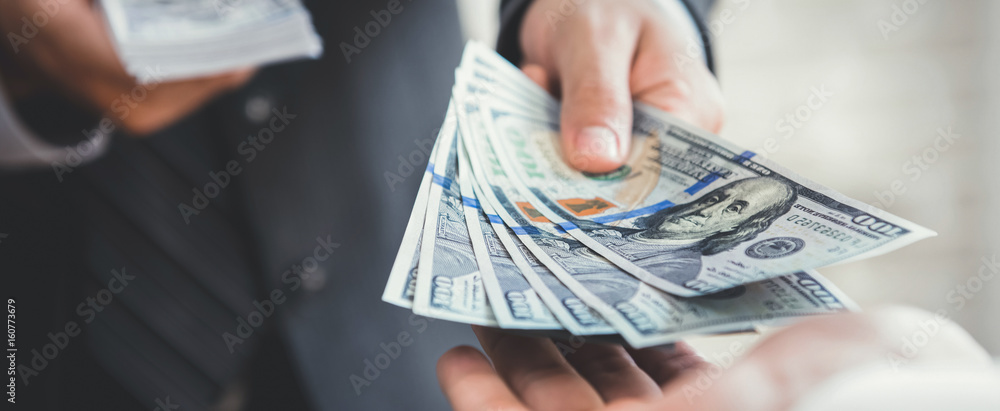 Fototapeta Businessman giving or paying money, US dollar bills
