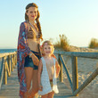 smiling mother and daughter outdoors in summer evening on beach