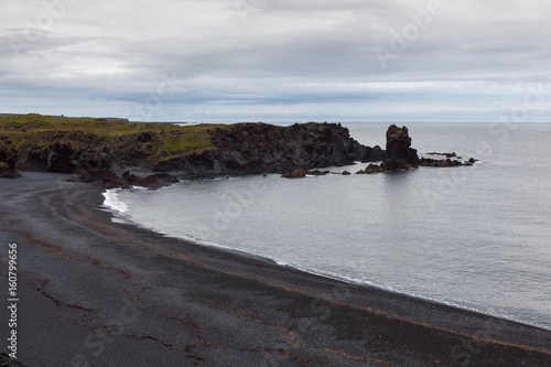 Foto op Plexiglas Noord Europa Aerial view over black beach in Snaefelsness peninsula, Iceland. Beautiful seashore landscape with low gray clouds and cliffs standing out of the ocean.