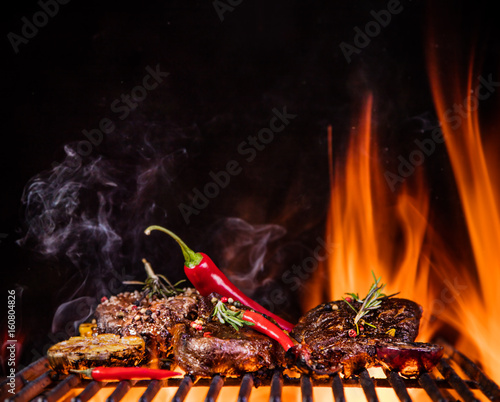 Foto op Plexiglas Grill / Barbecue Beef steaks on the grill with flames