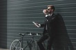Leinwanddruck Bild - stylish businessman with bicycle using digital tablet and drinking coffee while standing in front of black wall