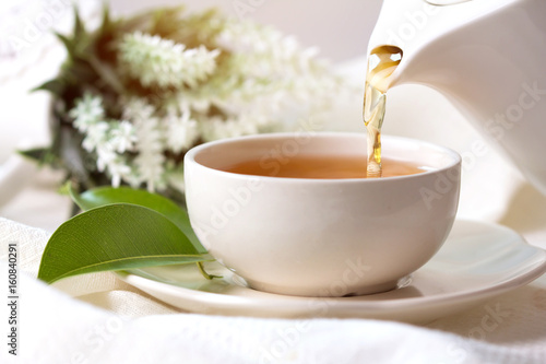 Poster Thee Close up pouring hot black tea in a white tea cup , Tea ceremony time concept