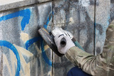 Fototapeta Młodzieżowe - Removal of graffiti on a concrete wall of an underground passage with the help of a angle grinder.