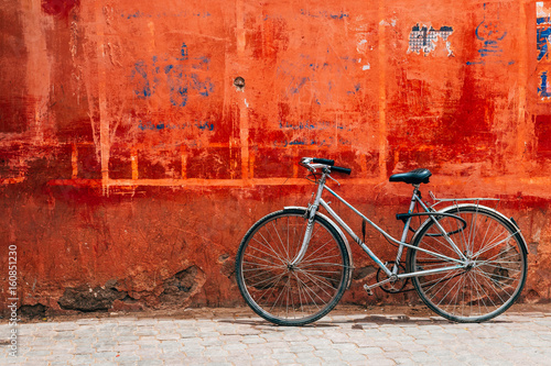 Deurstickers Fiets old bike standing at colorful red wall