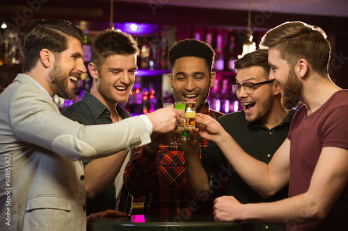 Photo Happy male friends drinking beer and clinking glasses