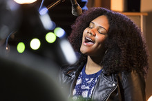 Black Female Singing In A Recording Studio