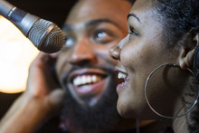 Black Male And Female Singing In A Recording Studio