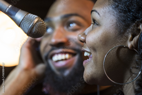 Photo  Black male and female singing in a recording studio