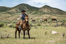Cowboy Wrangler Ranch Hand With Rope On Working Horse On Sage Brush Prairie
