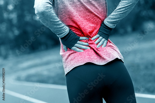 Cuadros en Lienzo  Athletic woman on running track touching hurt back with painful injury
