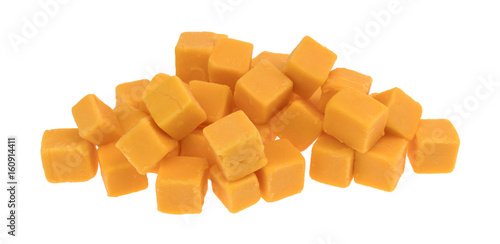 Cubed mild cheddar cheese in a pile isolated on a white background.