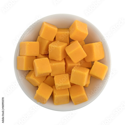 Cubed mild cheddar cheese in a white bowl.
