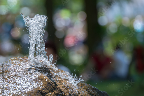 Fotografie, Obraz  Sprudelnde Wasserquelle aus einem Naturstein Springbrunnen