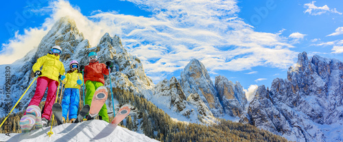 Garden Poster Winter sports Skiing family enjoying winter vacation on snow in sunny cold day in mountains and fun. San Martino di Castrozza, Italy.