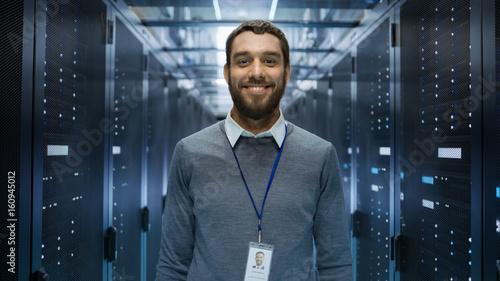 Plakat Portret ciekawostki, pozytywny i uśmiechnięty inżynier IT stojący w środku dużego pokoju serwerowni.