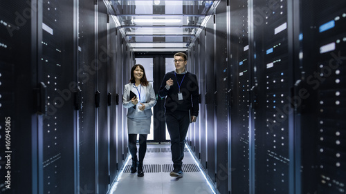 Fényképezés  Caucasian Male and Asian Female IT Technicians Walking through Corridor of Data Center with Rows of Rack Servers