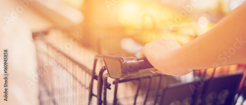 Fotografía Female Hand Close Up With Shopping Cart in a Supermarket Walking Trough the Aisl