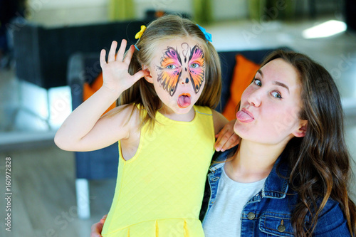 Photo Pretty girl with face painting of a butterfly with babysitter