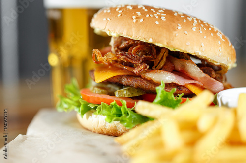 Big tasty burger and fries with beer on backround on the wooden table